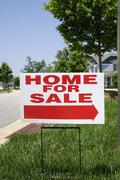'Home for sale' sign on the front lawn of a house Stock Photos