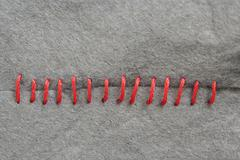Red stitching on gray fabric Stock Photos