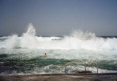 A person swimming into crashing waves Stock Photos