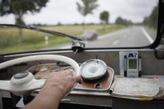 Close up of hand on steering wheel - stock photo