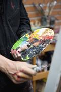 Detail of an artist holding a palette and painting knife - stock photo
