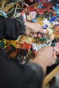 Detail of an artist mixing paint - stock photo