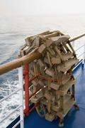 A rope ladder rolled up over a ship railing Stock Photos
