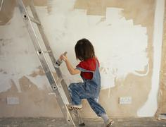 A young boy holding a paintbrush whilst climbing a ladder Stock Photos