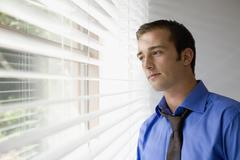 A young businessman staring out a window - stock photo