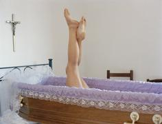 Naisen jalat nostaa pois avoimen arkun Kuvituskuvat