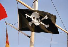 A skull and crossbones on a flag - stock photo