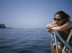 A woman sitting on a boat deck contemplation Stock Photos