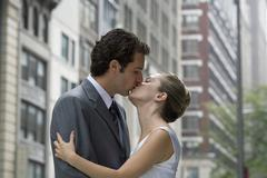 A bride and groom kissing in the street - stock photo