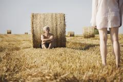 A naked man reclining against a hay bale facing a the back of a woman Stock Photos