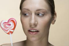 Portrait of a woman with a lollypop - stock photo