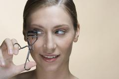 A woman using eyelash curlers - stock photo