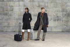 A man and woman waiting with luggage - stock photo
