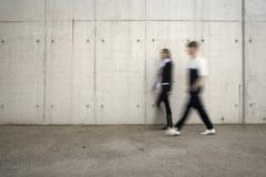Two people walking past a wall Stock Photos