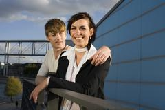 A couple standing next to railings overlooking a river - stock photo