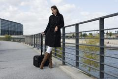 A woman standing on a bridge over a river with luggage Stock Photos