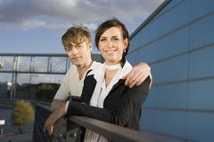 Stock Photo of A couple standing next to railings overlooking a river