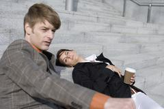 A couple resting on some steps with a take away coffee Stock Photos