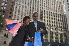 Stock Photo of Businessman and Businesswoman downtown with shopping bags