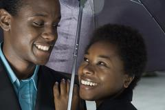 Man and Woman flirting under an umbrella - stock photo