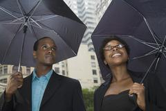 Man and woman downtown, each standing under an umbrella - stock photo