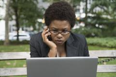 Businesswoman outside with laptop and mobile phone Stock Photos