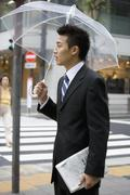 A businessman in the street with an umbrella Stock Photos