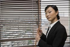 A businesswoman opening window blinds - stock photo