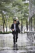 A businessman running in the rain Stock Photos