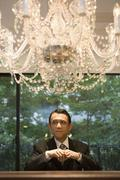 Stock Photo of A businessman standing underneath a chandelier