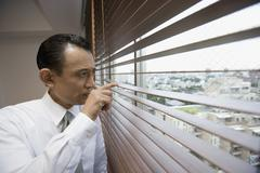 A businessman looking through window blinds Stock Photos