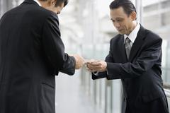 Two businessmen exchanging business cards - stock photo