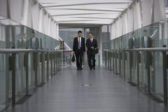 Two businessmen walking along a corridor Stock Photos