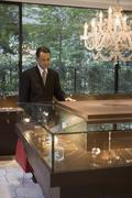 A businessman looking in a display cabinet in a jewelers - stock photo