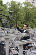 A businessman lifting his bicycle from a bicycle rack Stock Photos