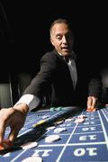 Well dressed man placing bet at roulette table - stock photo