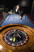 Man placing bet at the roulette table - stock photo