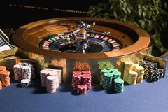 Roulette wheel with multiple stacks of gambling chips Stock Photos