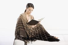 A woman wrapped in a blanket and reading a book Stock Photos