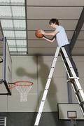 Nuori mies seisoo tikkailla valmistautuu pudottaa koripallo osaksi Kuvituskuvat