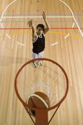 A young man shooting a basketball into a basketball hoop - stock photo