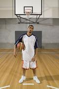 A young man standing on a basketball court with a basketball Stock Photos