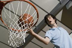 A man standing above a basketball hoop - stock photo