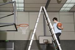 A man climbing up a ladder next to a basketball hoop - stock photo
