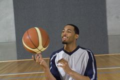A young man spinning a basketball on his finger Stock Photos