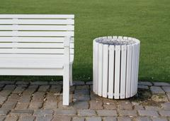 Stock Photo of A white bench and rubbish bin