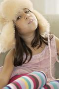 A young girl wearing a hunter's cap and blowing a bubble gum bubble Stock Photos