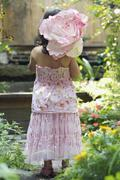 A Rear View of a young girl dressed up standing in a garden and carrying a paper Stock Photos