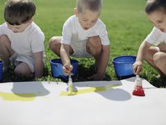 Three boys painting on paper outside - stock photo