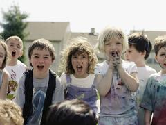 A medium group of children in paint splattered clothes yelling at the camera Stock Photos